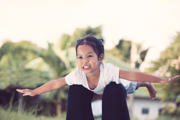 Happy asian child girl laughing and having fun to play with her mother in the park in vintage color tone