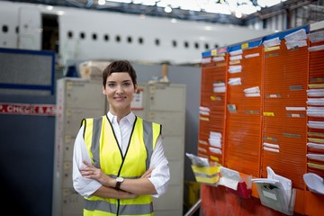 Female aircraft maintenance engineer standing with arms crossed