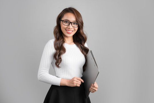 Portrait of young confident asian female teacher with folder