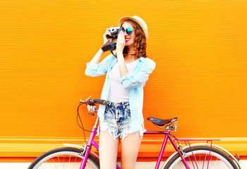 Summer pretty woman with retro camera and bicycle on a colorful orange background