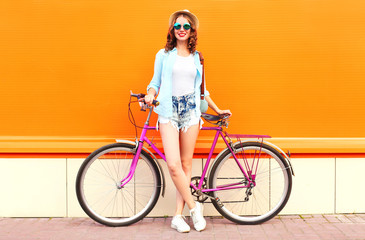 Summer smiling woman with bicycle on a colorful orange background