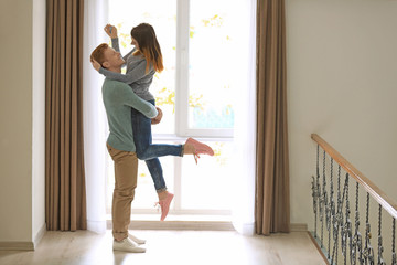 Happy young couple near window in new flat