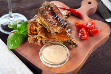 Delicious ribs served for dinner on wooden board