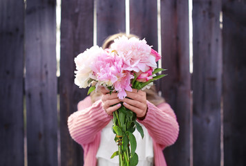 Beautiful young woman with bouquet of peonies near wooden fence