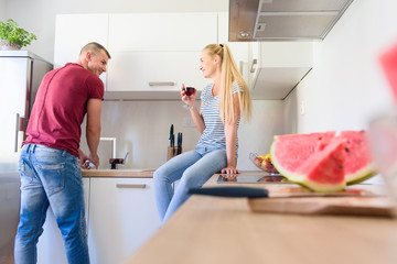 Attractive young caucasian man waghing up dishes, while his girlfriend who is sitting on kitchen counter, holds glass of red wine
