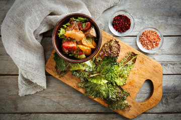 Bowl with salad and lettuce chips on wooden board
