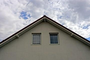 фасад серого дома с маленькими окнами на фоне неба и облаков