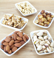 Assorted mixed nuts in black plate on white background