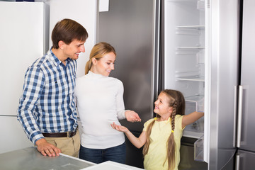 Smiling family with girl choosing refrigerator
