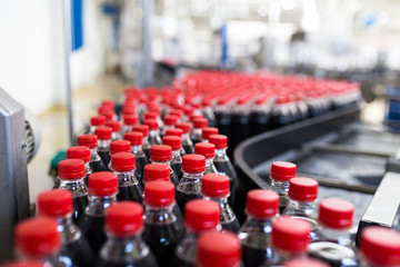 Bottling factory - Black juice or soft drink bottling line for processing and bottling juice into bottles. Selective focus.