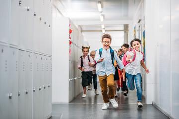 pupils running through school corridor
