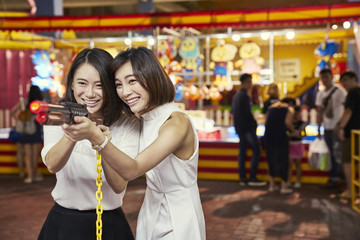 Girlfriends having fun at a carnival in Singapore