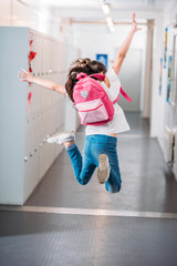 girl jumping in school corridor
