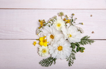 A bouquet of white flowers cosmea or cosmos with ribbon on white boards. Garden yellow flowers over handmade wooden table background. Backdrop with copy space.