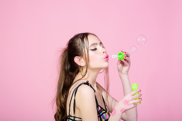 woman with bubble blower on pink studio background