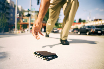 Wallet: Man Stoops Over To Pick Up Dropped Wallet