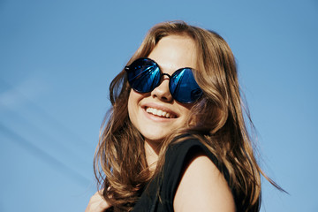 Woman in sunglasses smiling, portrait, street