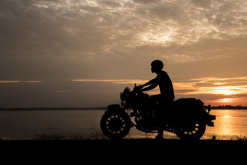 Silhouette man riding motor bike with sunset. Travel Concept