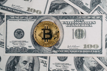Golden bitcoin on top of dollar bill and dollar banknote background, new currency replacement concept.