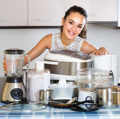 Housewife posing with kitchen appliances