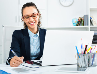 Business lady sitting at office desk with laptop