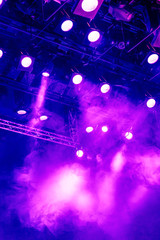 Purple light rays from the spotlight through the smoke at the theater or concert hall. Lighting equipment for a performance or show.