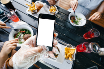 Male blogger makes photos of food on your smartphone in a glove to avoid soiling the hands with friends. Photo of food..