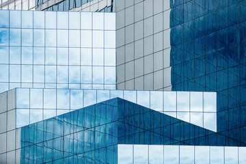 Obraz Blue sky and clouds reflecting in windows of modern office building - fototapety do salonu