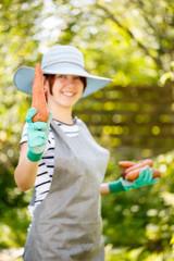 Girl in gloves holds carrot