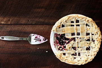 Top view of a blueberry pie with lattice and stars crust over a rustic wooden background. A slice of the pie is missing. Image shot from above.