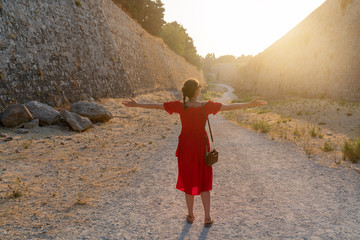 girl goes to meet a bright sun near the ramparts of the island of Rhodes in Greece