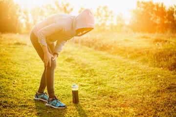 Injuries - sports running knee injury on woman. Detox smoothie.