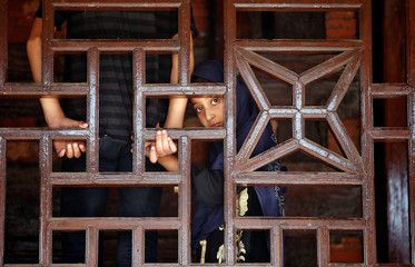 A Muslim girl looks on behind a wooden window frame at the shrine of Mir Syed Ali Hamdani, a Sufi saint, during an annual religious festival in Srinagar