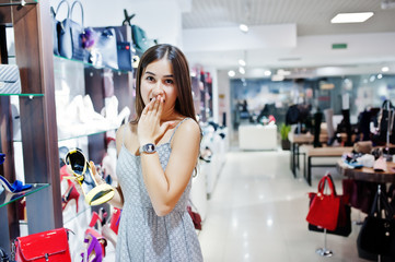 Flawless young woman holding yellow high-heeled shoe.