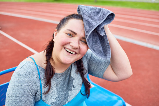 Sweaty and happy fat woman drying her forehead with towel after hard workout