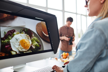 Professional food designer retouching photo while sitting in front of modern computer, spacious production studio with panoramic windows on background