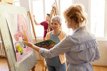 artists discussing painting on easel at art school