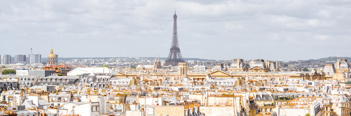 Aerial panoramic cityscape view on the beautiful buildings and Eiffel tower on the horizon during the cloudy weather in Paris