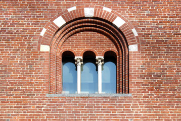 Mullioned window with three lights on a brick wall