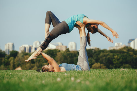 Two young beautiful Caucasian women yogi doing high flying whale acro yoga pose. Women doing stretching workout in park outdoors at sunset. Healthy lifestyle modern activity