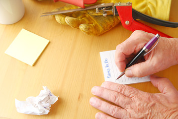 Overhead of man writing a to do list with crumpled paper, notepad, coffee cup, gardening glove and grass cutters