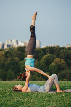 Two Caucasian women yogi doing shoulder stand candlestick acro yoga pose. Women doing stretching workout in park outdoors at sunset. Healthy lifestyle modern activity