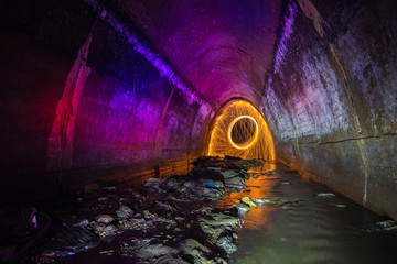 Sewer tunnel illuminated by color lanterns and freezelight using spinning burning steel wool and pyrotechnics