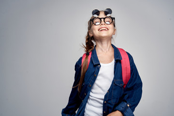 little girl smiling with a backpack on a gray background