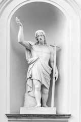 White marble sculpture of holy man with a cross and uplifted hand