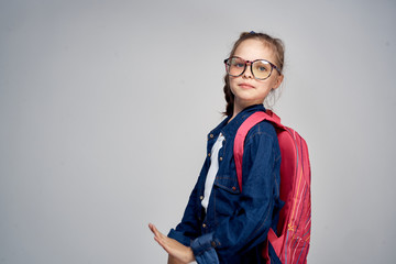 little girl with glasses with a backpack, empty space for copying