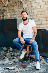 a handsome brutal man with a beard in jeans and a white T-shirt on the background of a gray brick wall and construction debris