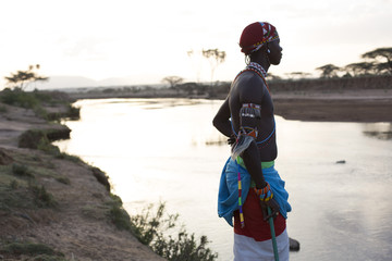Samburu tribesman, standing by river in the early morning light, Kenya, Africa.
