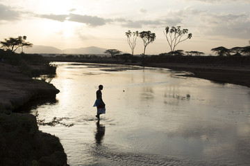 Samburu tribesman walking across river, in early morning light. Kenya, Africa.