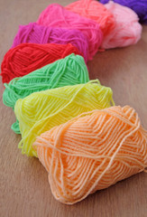 Set of rainbow color wool yarns for knitting on wood